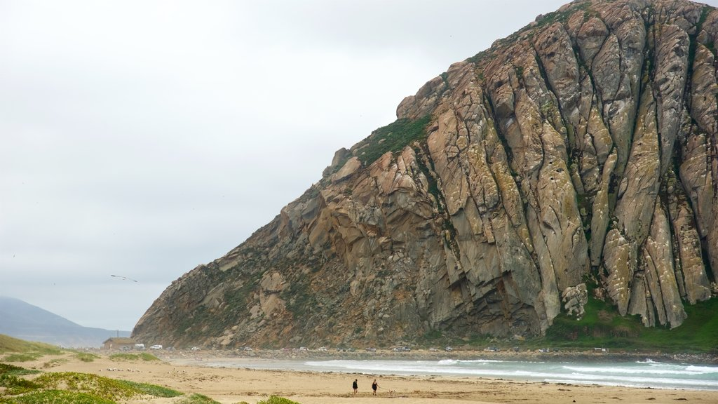 Morro Rock featuring a sandy beach, general coastal views and mountains