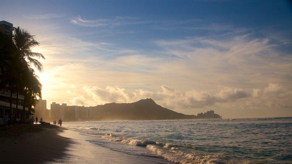 Waikiki Beach showing rugged coastline, surf and a sunset