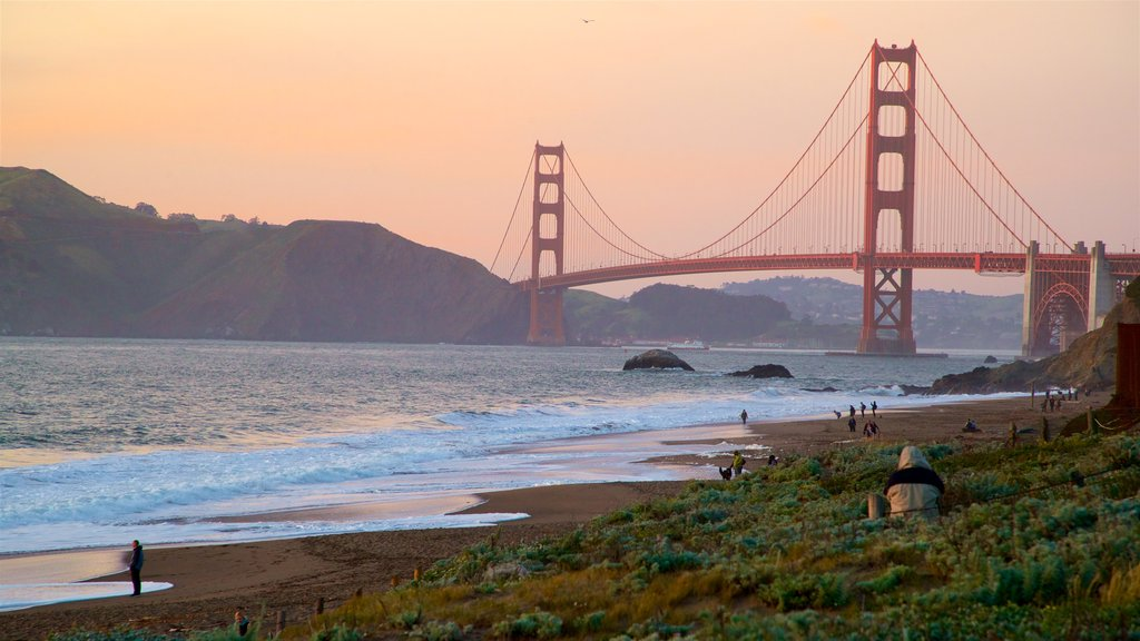Golden Gate Bridge showing surf, a sunset and a bridge