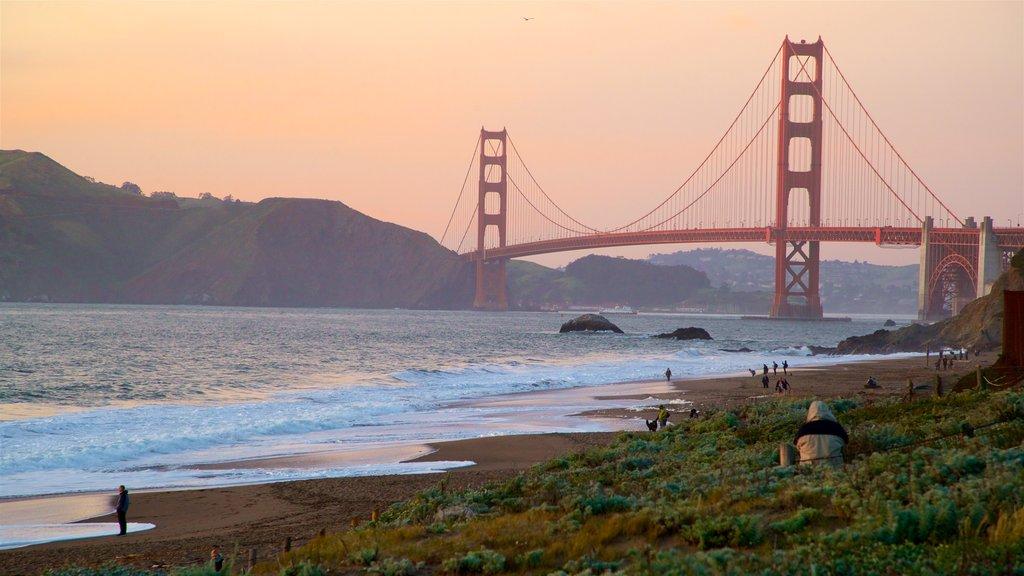 Puente Golden Gate que incluye una puesta de sol, un puente y olas