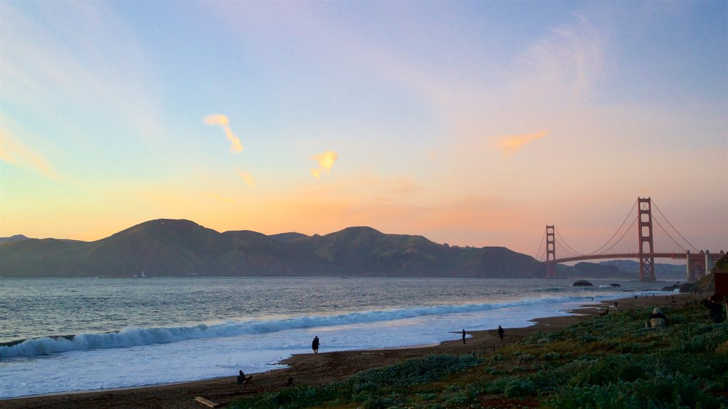 Golden Gate Bridge featuring a sunset, waves and a bridge