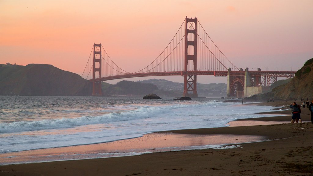 Golden Gate Bridge showing waves, a sunset and a bridge