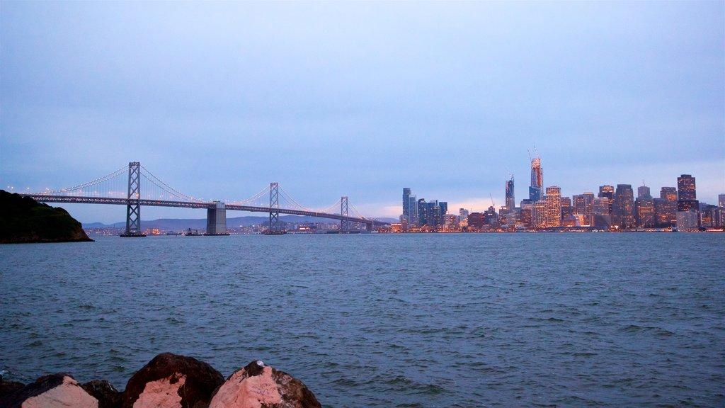 Isla Treasure que incluye una puesta de sol, un río o arroyo y un rascacielos