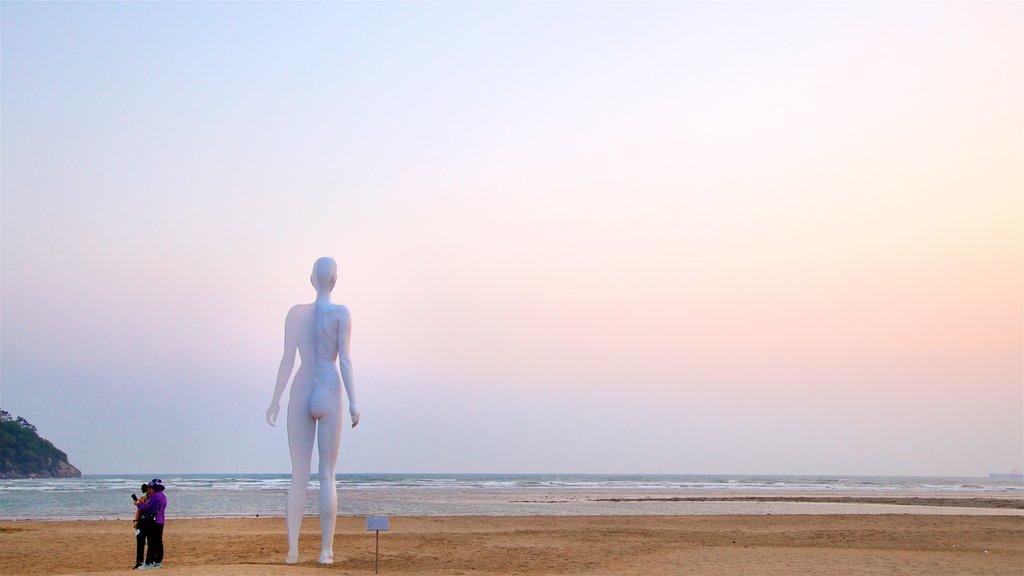 Playa de Dadaepo mostrando arte al aire libre, una puesta de sol y vistas generales de la costa
