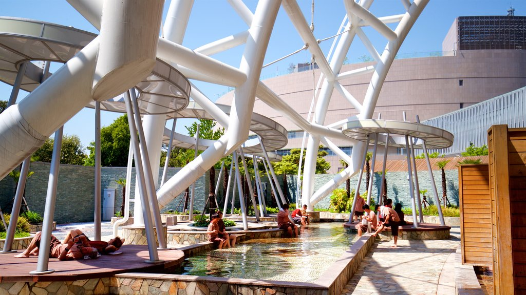 Shinsegae Centum City showing a pool and a luxury hotel or resort as well as a small group of people
