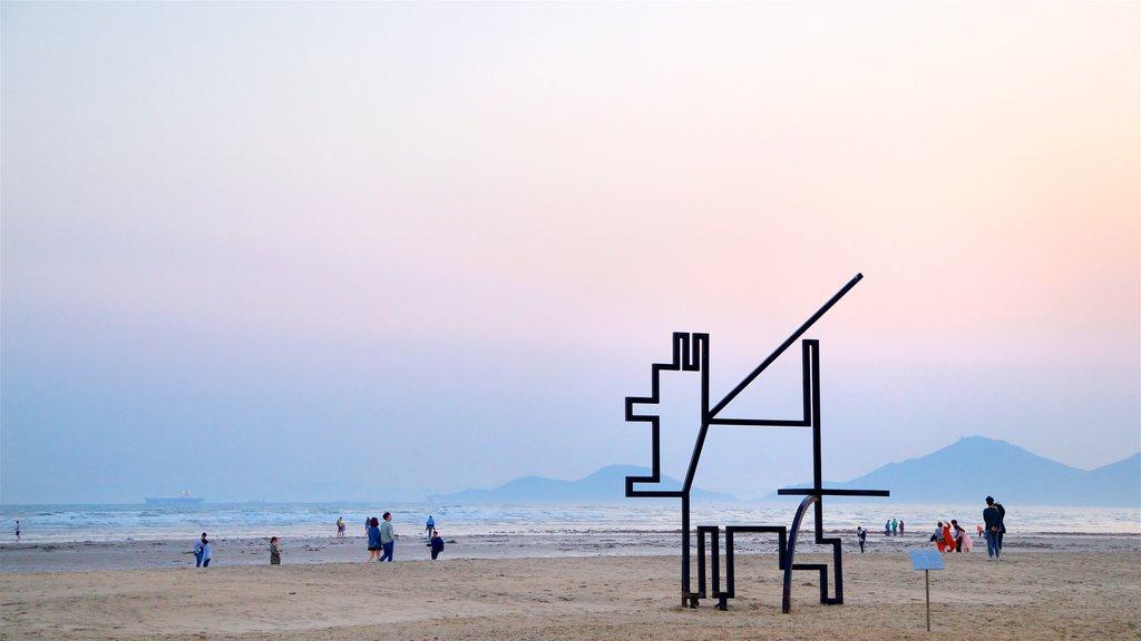 Playa de Dadaepo ofreciendo arte al aire libre, vistas generales de la costa y una puesta de sol
