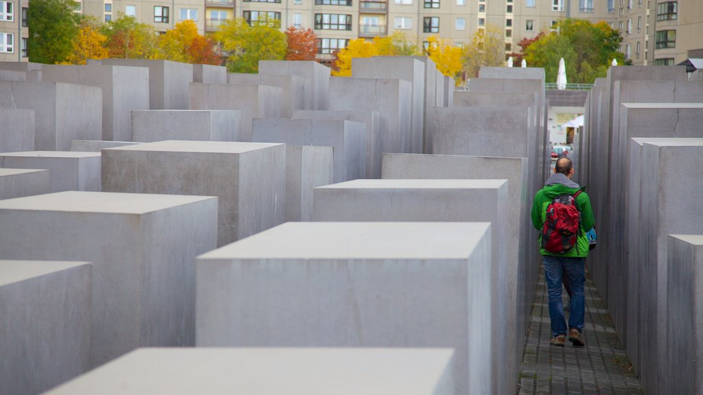 Holocaust Memorial showing a memorial and a city as well as an individual male