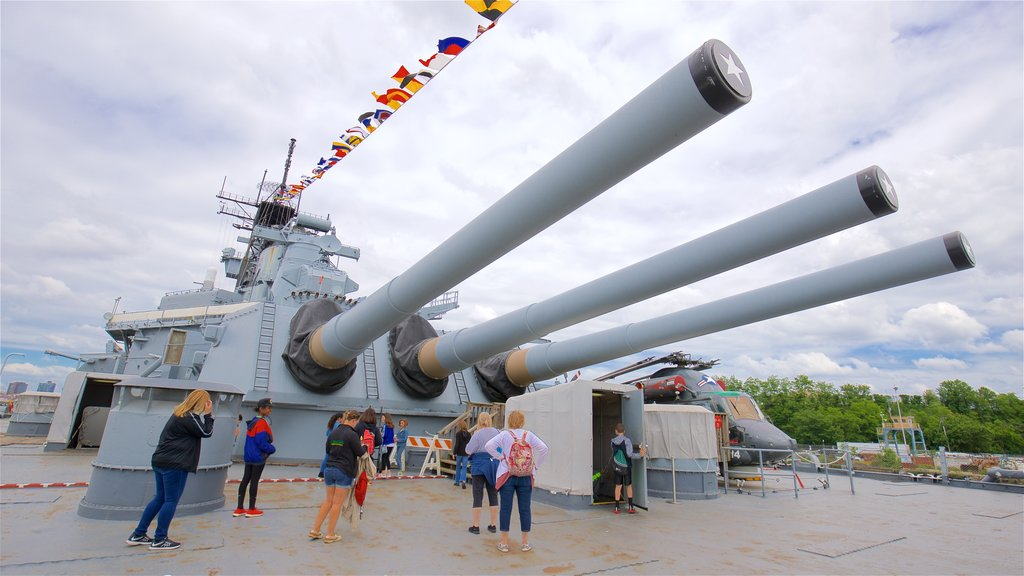 Battleship New Jersey which includes military items and a marina as well as a small group of people