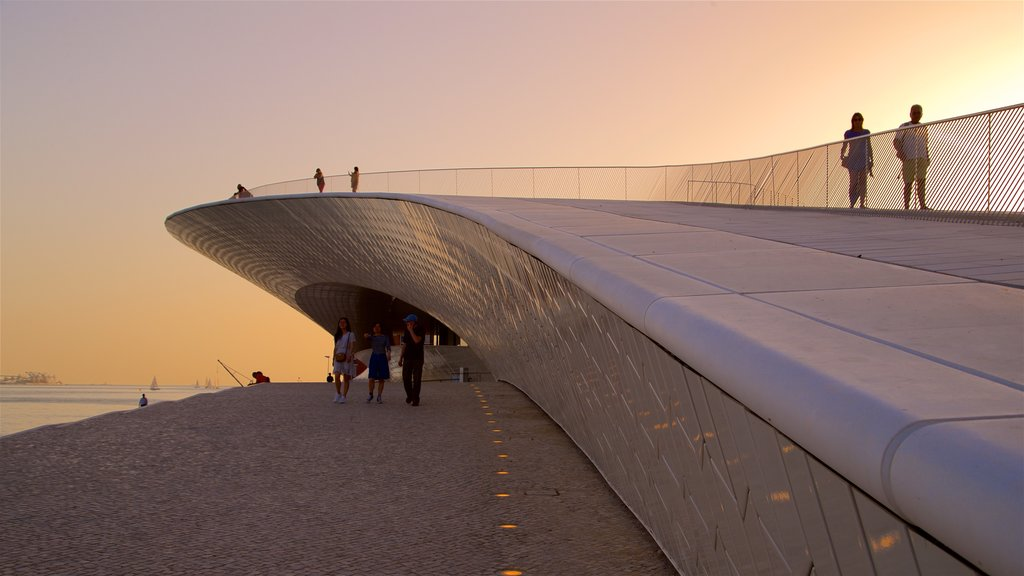 Lisbon District which includes a sunset and modern architecture as well as a small group of people
