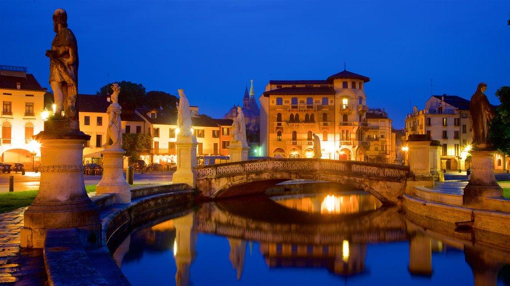Prato della Valle featuring a statue or sculpture, night scenes and a river or creek