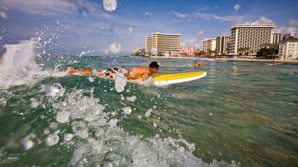 Waikiki showing waves, city views and tropical scenes