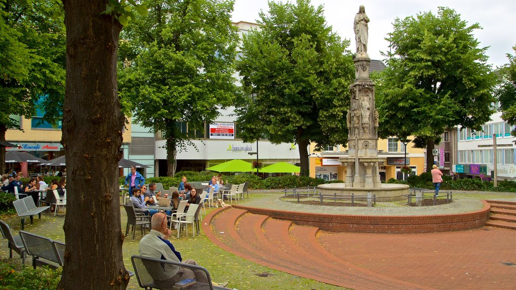 Marienplatz Paderborn featuring a statue or sculpture and a fountain as well as a small group of people