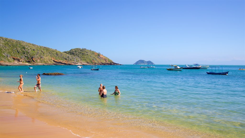 Joao Fernandes Beach featuring a sandy beach, rocky coastline and swimming
