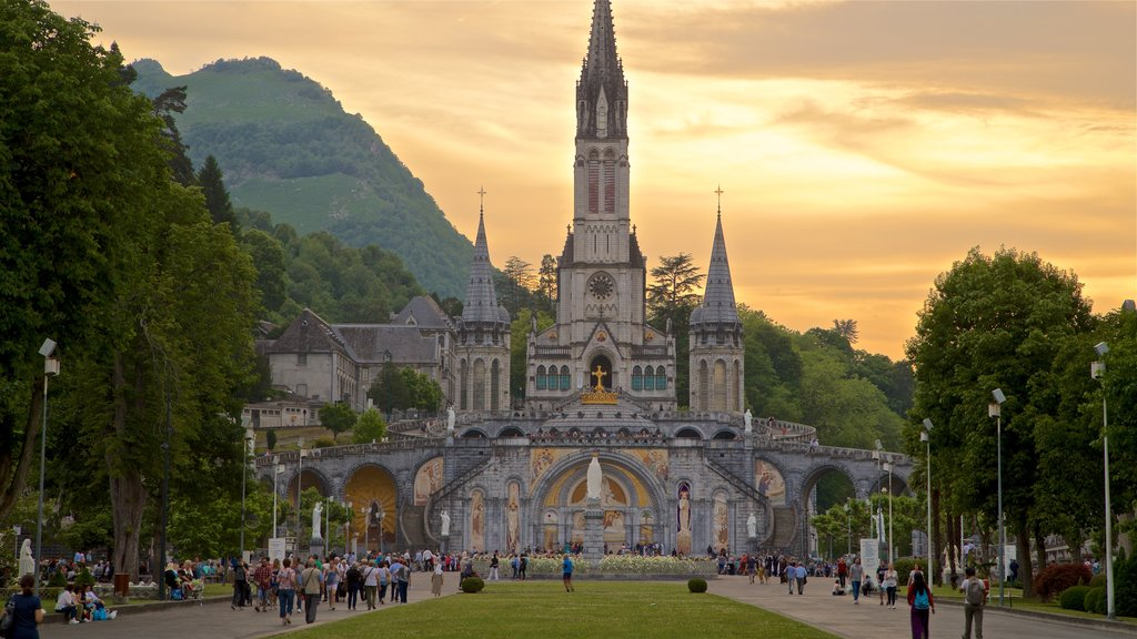 Lourdes which includes heritage architecture, a church or cathedral and a sunset