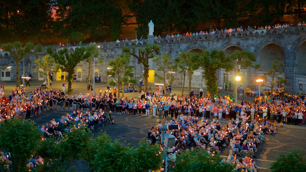 Lourdes featuring a square or plaza as well as a large group of people
