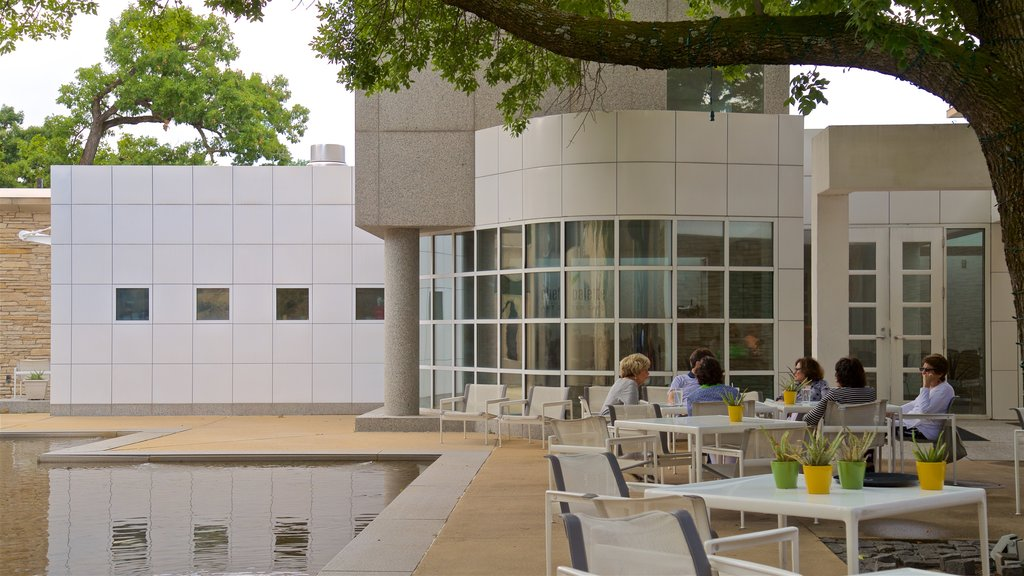 Des Moines Art Center featuring outdoor eating and a pond as well as a small group of people
