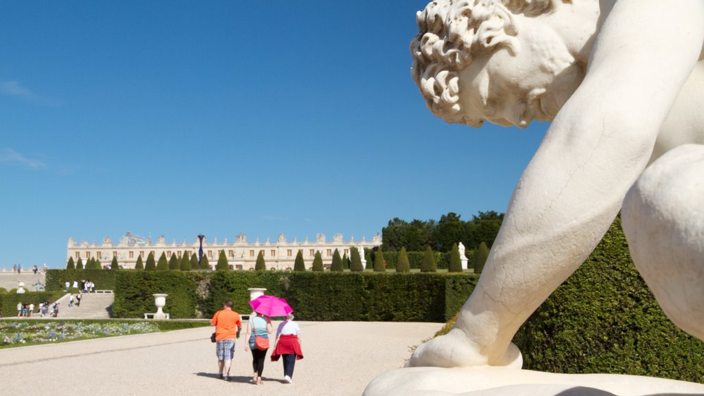 Versailles featuring a statue or sculpture, a garden and chateau or palace