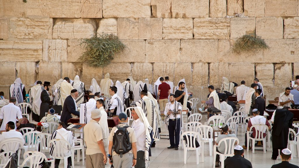 Western Wall featuring religious aspects and heritage elements as well as a small group of people