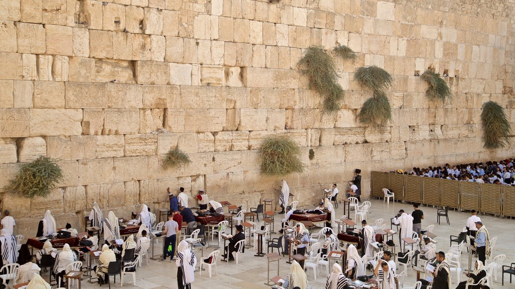 Western Wall showing religious aspects and heritage elements as well as a small group of people