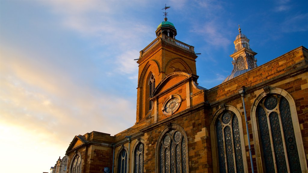 All Saints Church which includes a sunset and heritage architecture