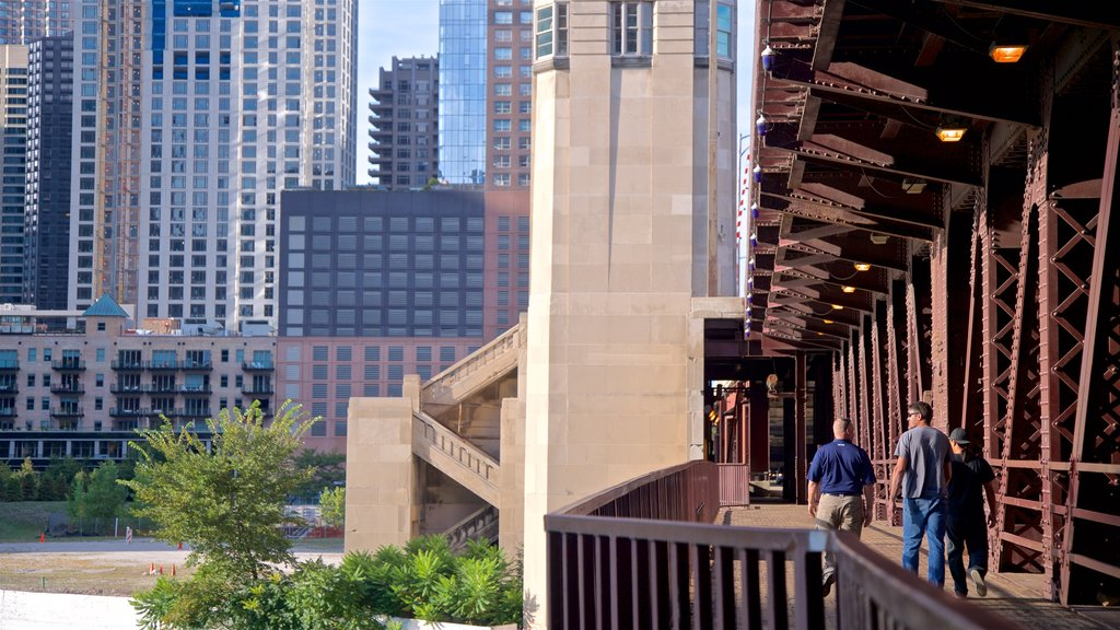 Chicago Riverwalk which includes a city and a bridge as well as a small group of people