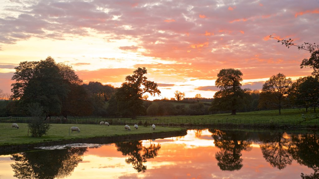 Broughton Castle featuring a sunset, landscape views and farmland