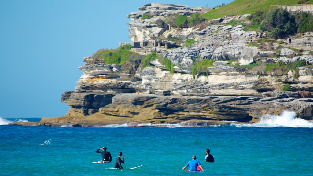 Bondi Beach showing rocky coastline, general coastal views and surfing
