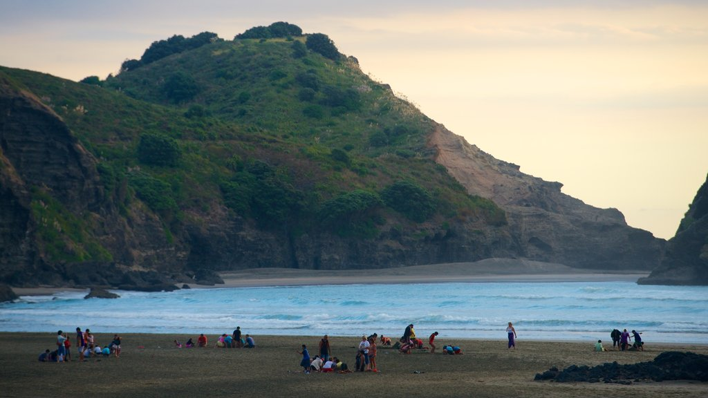 Piha Beach ofreciendo una puesta de sol, una playa de arena y vistas de paisajes