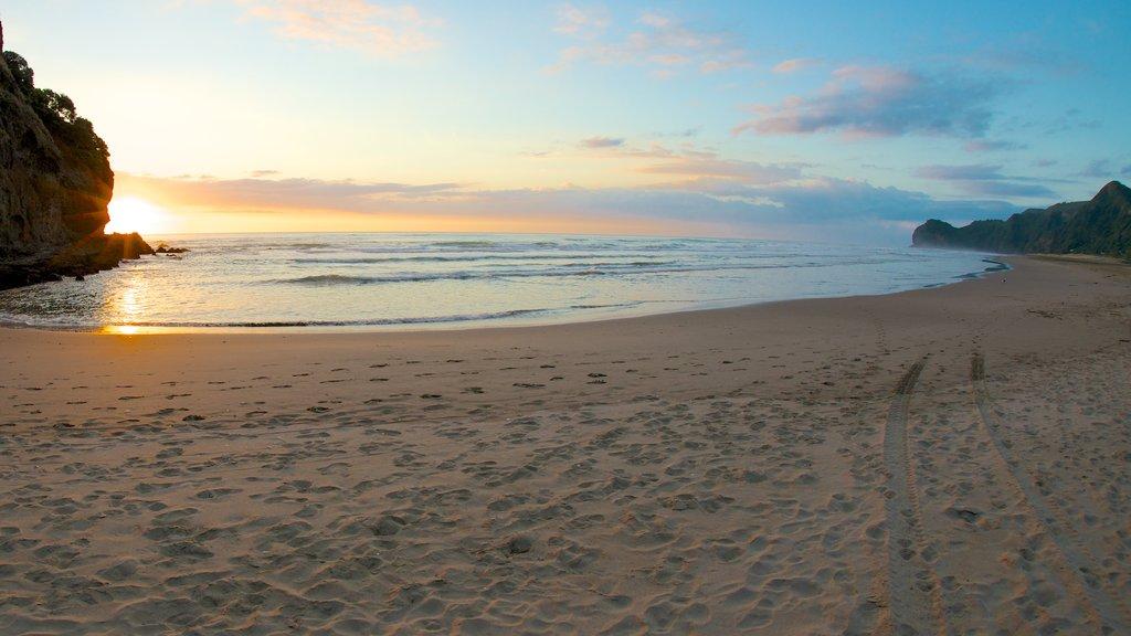 Piha Beach ofreciendo una puesta de sol, vistas de paisajes y una playa