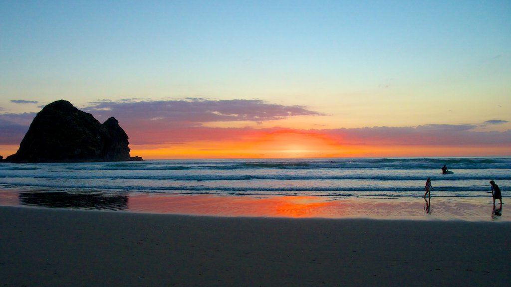 Piha Beach which includes landscape views, a sandy beach and a sunset