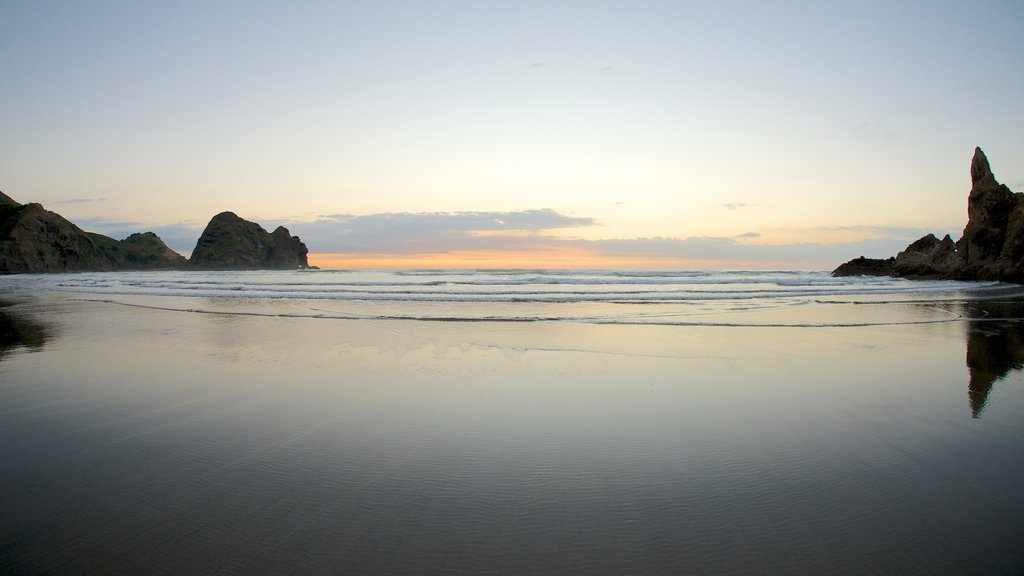 Piha Beach featuring a sunset, a beach and general coastal views