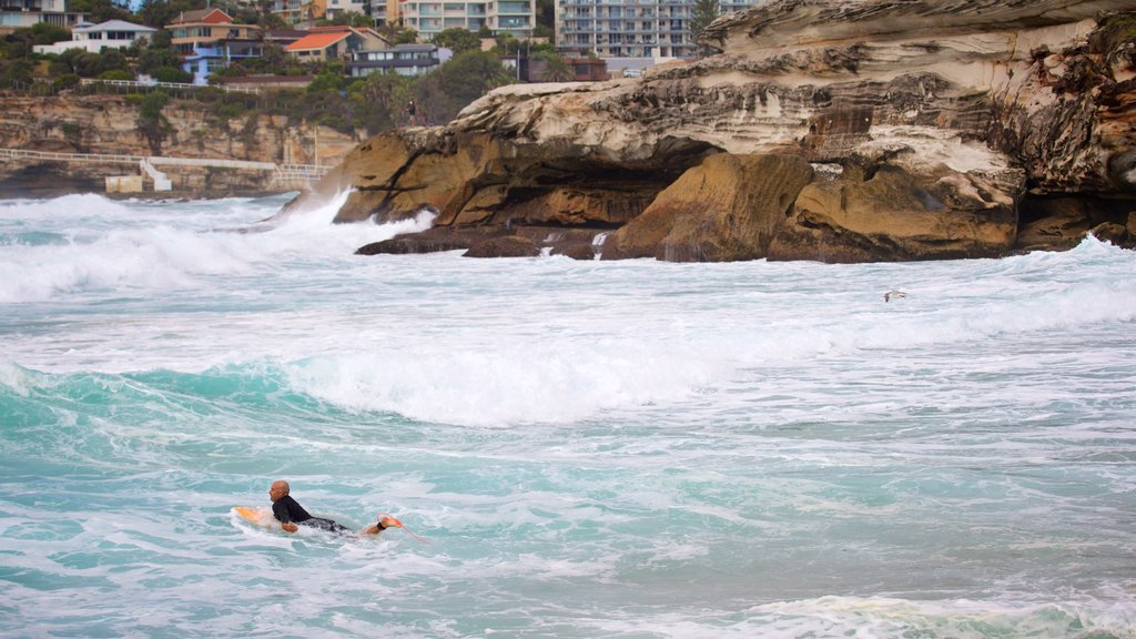 Tamarama Beach which includes rocky coastline, surfing and general coastal views