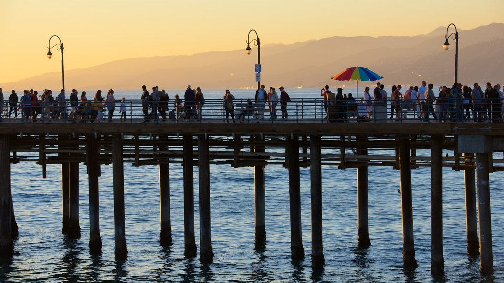 Santa Monica Pier showing a sunset and general coastal views as well as a large group of people