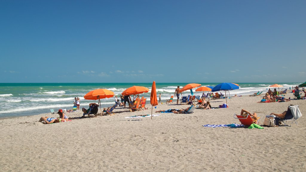 Cocoa Beach featuring a sandy beach and general coastal views as well as a small group of people