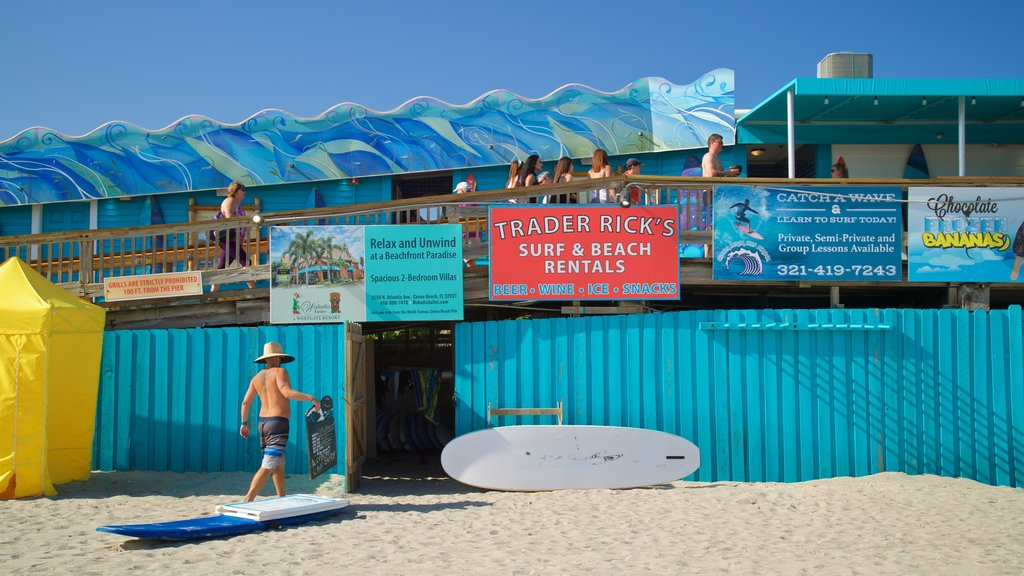 Cocoa Beach Pier which includes a beach and signage as well as an individual male