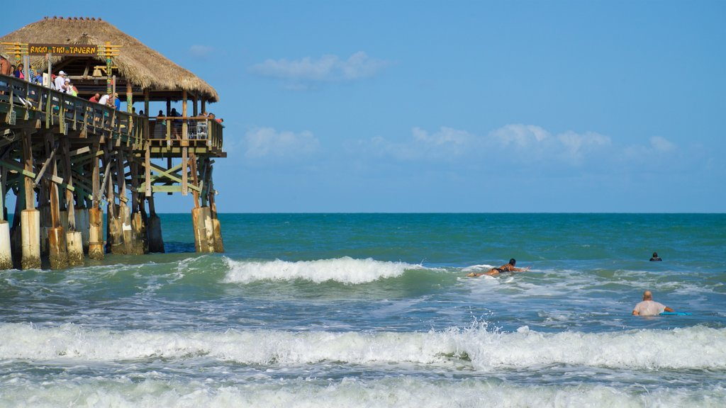 Cocoa Beach Pier featuring swimming and general coastal views as well as a small group of people