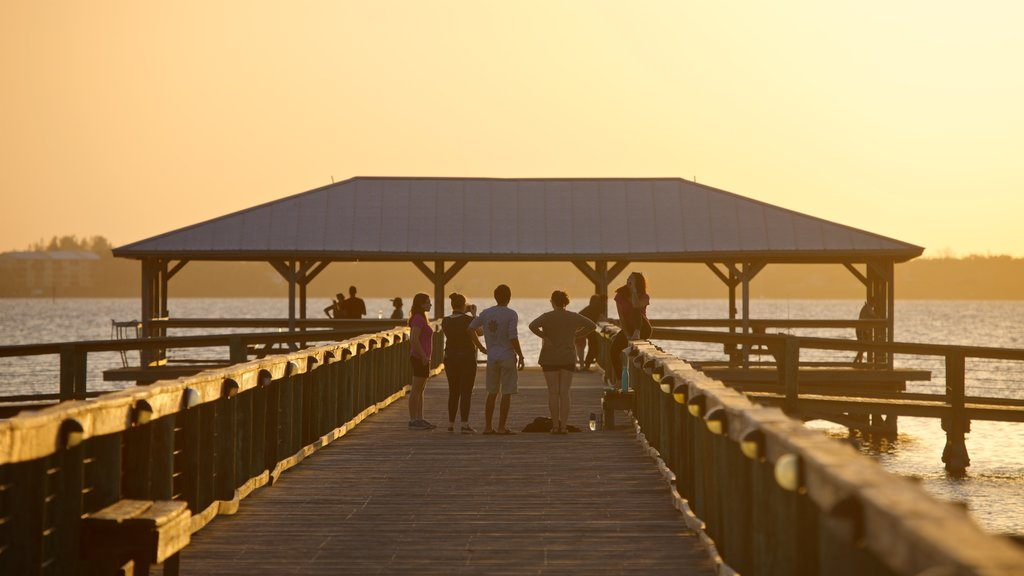 Melbourne Beach featuring a sunset and general coastal views as well as a small group of people