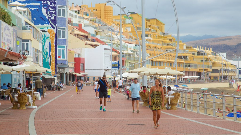 Playa de Las Canteras featuring a coastal town and general coastal views as well as a small group of people
