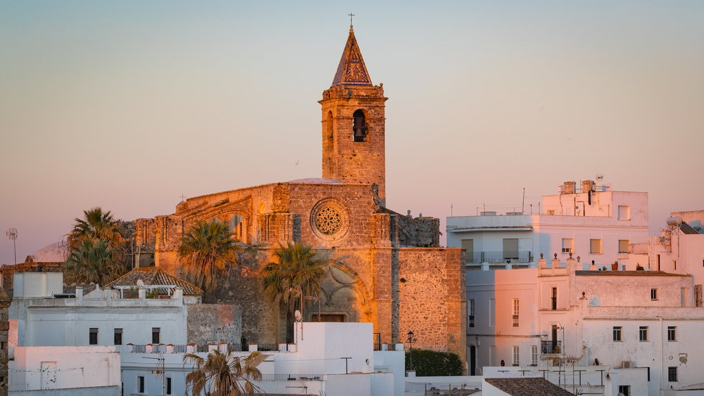 Vejer de la Frontera showing a church or cathedral, heritage architecture and a sunset