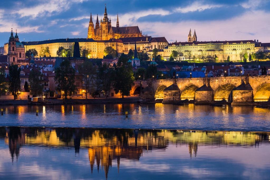 Tra le cose da fare a Praga: visita al Castello e al Ponte Carlo al tramonto riflessi sul fiume Vltava - Photo credit Shutterstock