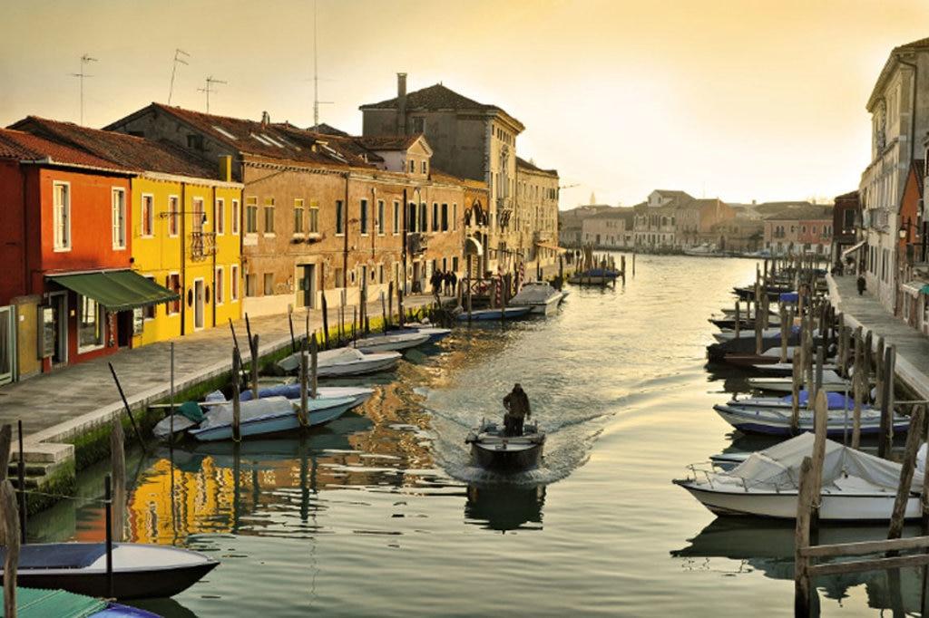 Un uomo in barca lungo un canale di Murano - Photo credit Shutterstock