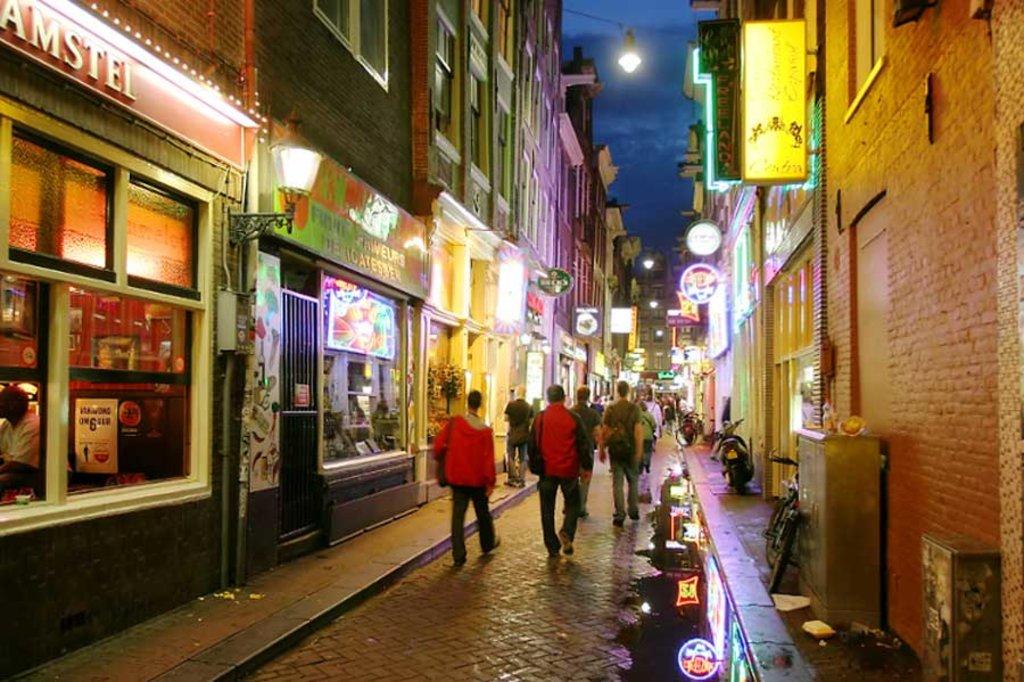 Alcuni turisti percorrono una delle tante vie del quartiere a luci rosse, invase soprattutto di sera, dagli amanti della movida - Photo credit Shutterstock