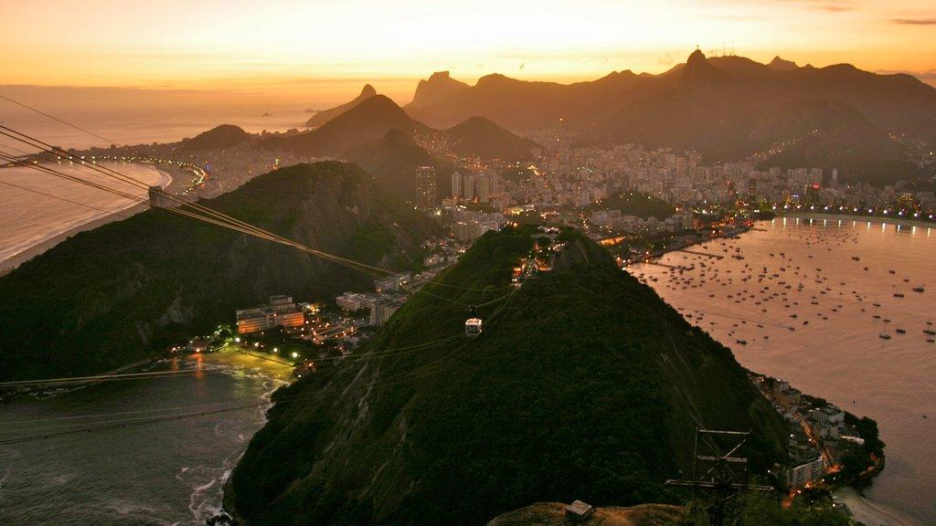 Río de Janeiro que incluye una puesta de sol, montañas y vistas generales de la costa