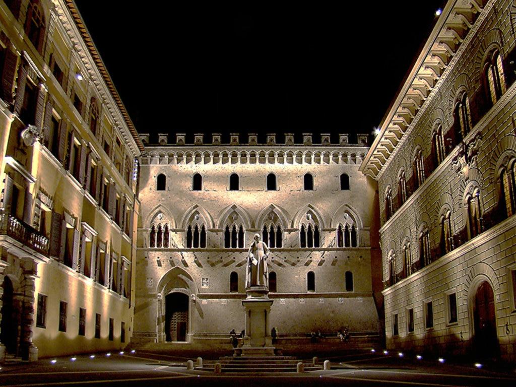 Veduta notturna di Piazza Salimbeni con il Palazzo Salimbeni al centro, il Palazzo Tantucci a sinistra e il Palazzo Spannocchi a destra - Di Tango7174 - Opera propria, GFDL, https://commons.wikimedia.org/w/index.php?curid=8898309