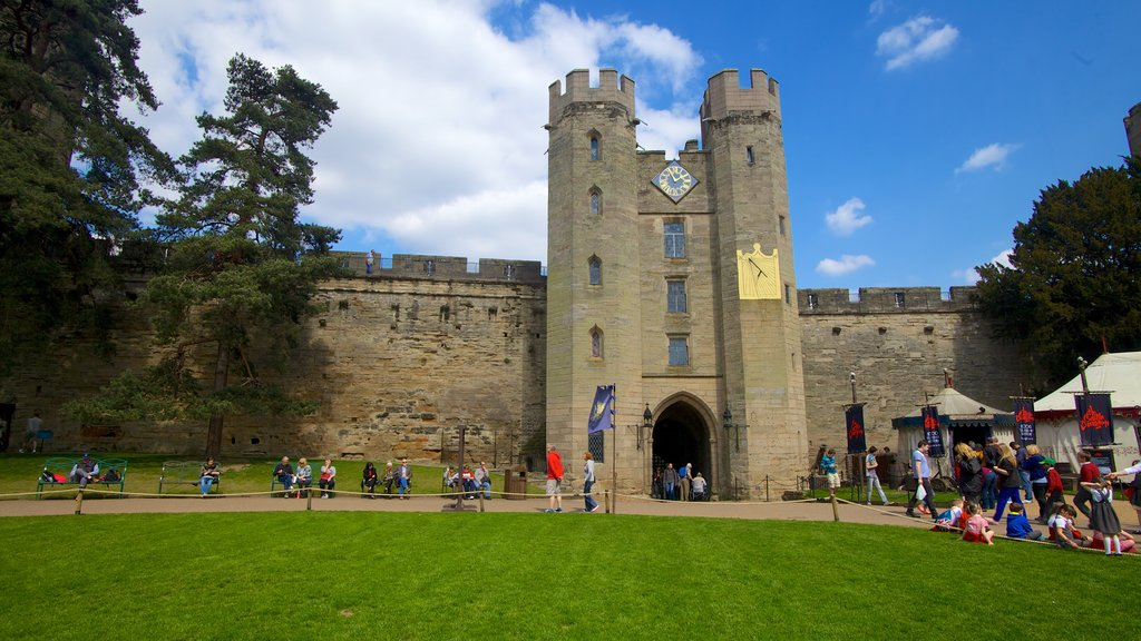 Warwick Castle showing heritage architecture and a castle as well as a large group of people