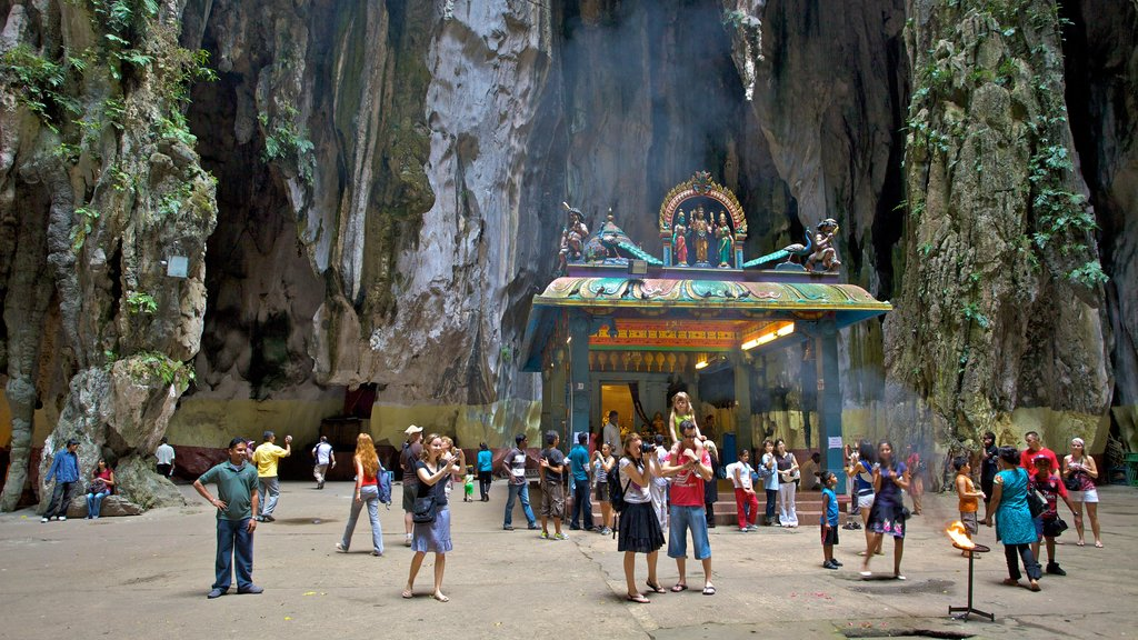 Batu Caves featuring caves as well as a large group of people