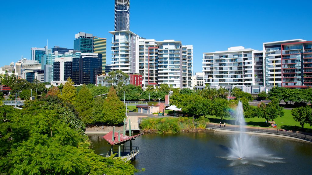 Roma Street Parkland featuring a fountain, a skyscraper and a pond