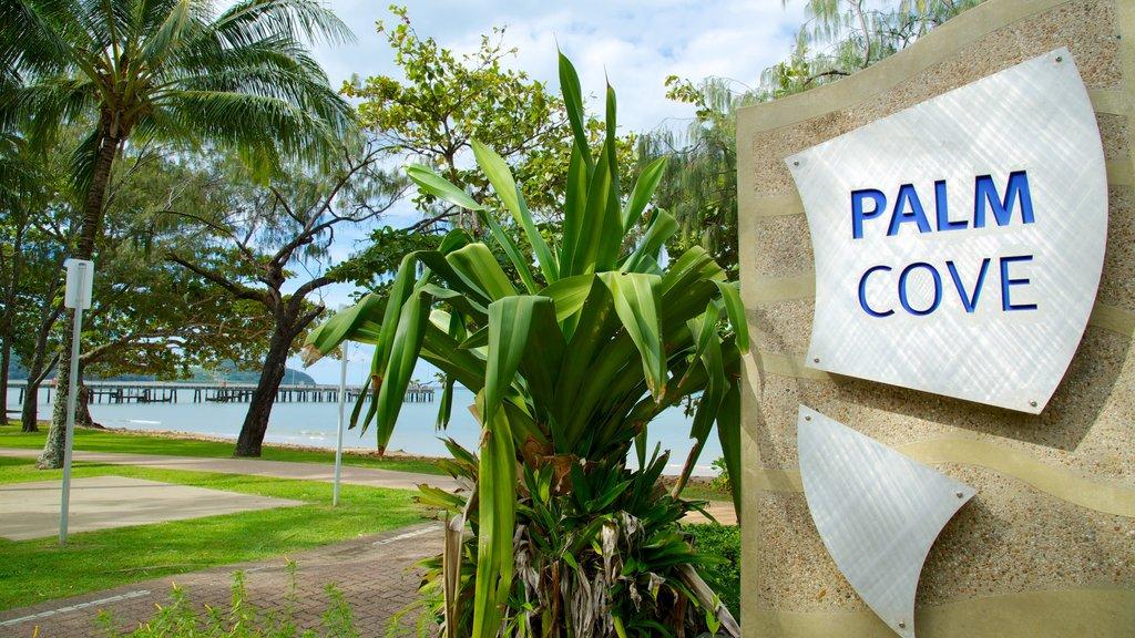 Palm Cove Beach ofreciendo escenas tropicales, un jardín y señalización