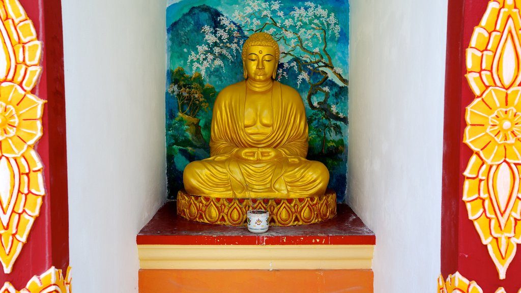 Dhammikarama Burmese Buddhist Temple showing a statue or sculpture, a temple or place of worship and religious aspects