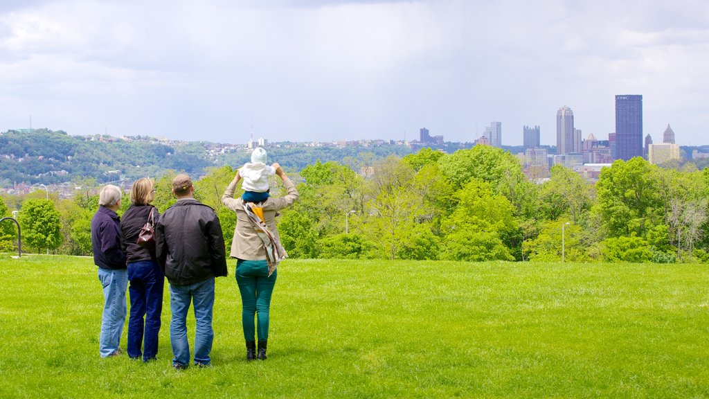 Schenley Park featuring skyline and a garden as well as a small group of people